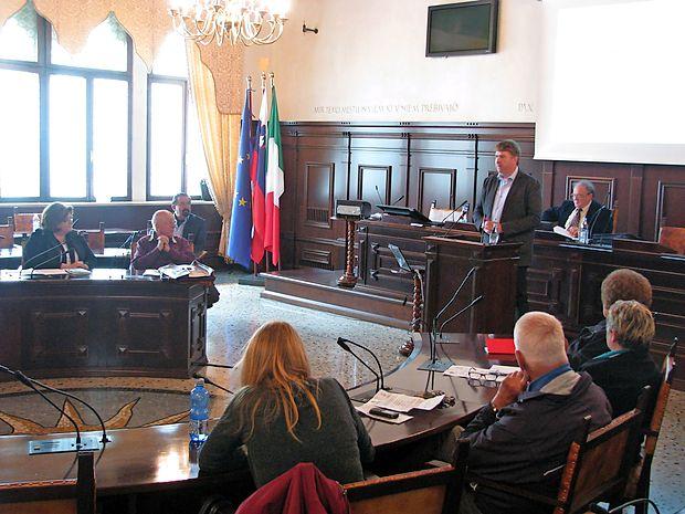 Na posvetu v koprski Pretorski palači so o Gentilijevi reformi govorili Rok Svetlič (za govorniškim odrom), Miloš  Ivančič (zadaj), Nadja Terčon (sedi skrajno levo), Jože Pirjevec (sedi) in Egon Pelikan (sedi v drugi vrsti).