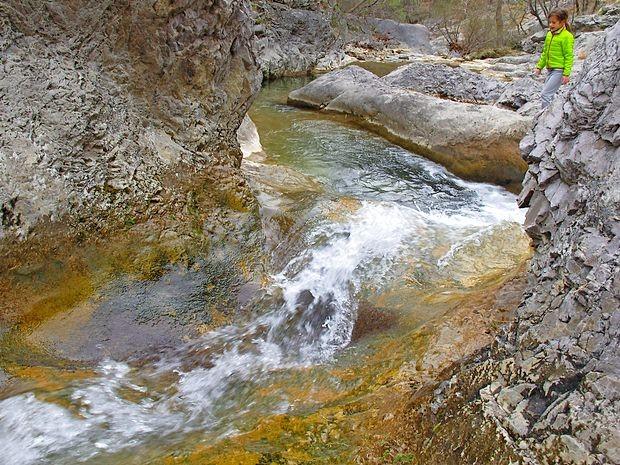 Na dnu globeli po zglajenih skalah žubori plitev  potok.