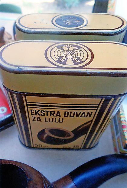 Lesene ali pločevinaste škatle za tobak so sprva  imele  grb  kraljevine SHS,  po drugi svetovni vojni so ga pobarvali in ga  kasneje spremenili v grb Federativne narodne Republike  Jugoslavije.  janez janežič