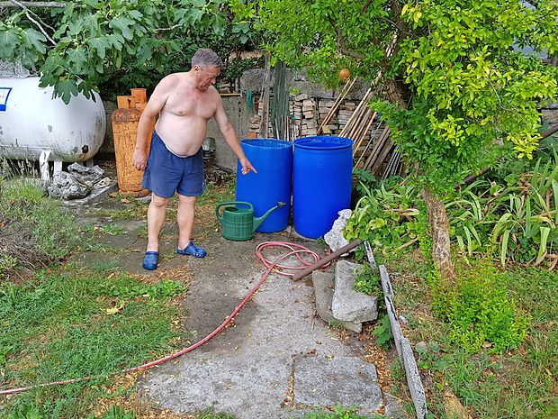 Domačin Slavko Dobrin kaže, kje na vrtu ima nameščeno  greznico.