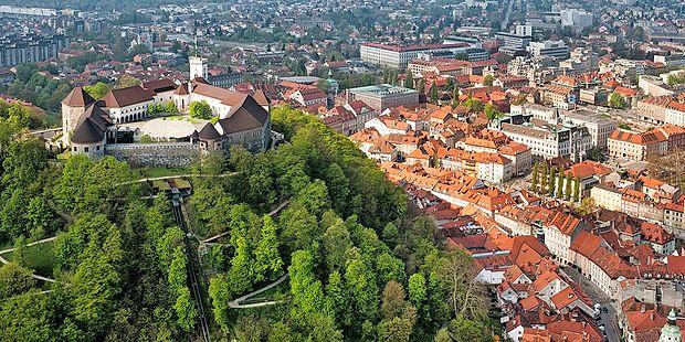 Ljubljanski grad kraljuje na zelenem griču nad zgodovinskim  delom mesta.