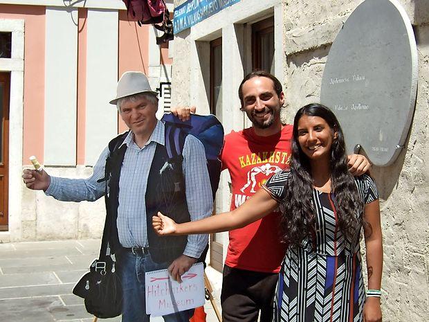"""Svetovna popotnika, Argentinca   Eric  Lansome in Ayu Santana, sta se v Piranu za šalo postavila ob """"kartonastega""""  Mirana Ipavca, ki usmerja obiskovalce v avtoštoparski muzej."""