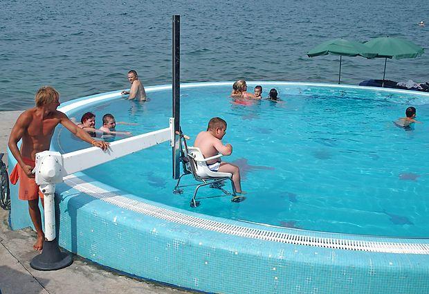 Osebam z živčno-mišičnimi obolenji s posebnim dvigalom  omogočajo dostop v ogrevan bazen na izolski plaži invalidov.    društvo distrofikov slovenije