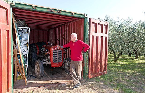 Dino Pucer pred svojim kontejnerjem, v katerem ima naprave  in orodje za obdelovanje oljčnika.