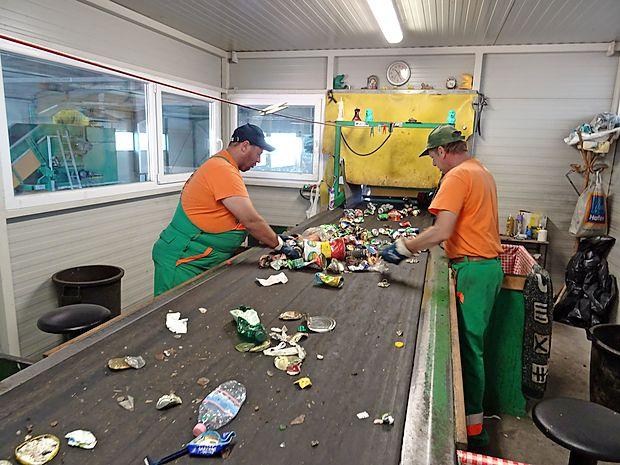 Na tekočem traku v sežanskem centru za ravnanje z odpadki  ročno ločijo aluminijaste pločevinke od železnih. Plastenke  pa ločujejo po barvah.