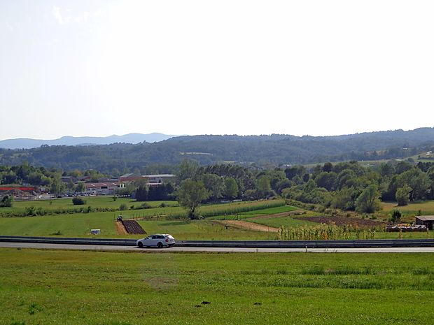 Od Šercerjeve ceste (kjer je avto) do Vilharjeve (hiše v ozadju) naj bi potekal še manjkajoči del  obvoznice, navezal pa bi se  na krožišče pred Topolcem, kjer se zdaj začne obvoznica.