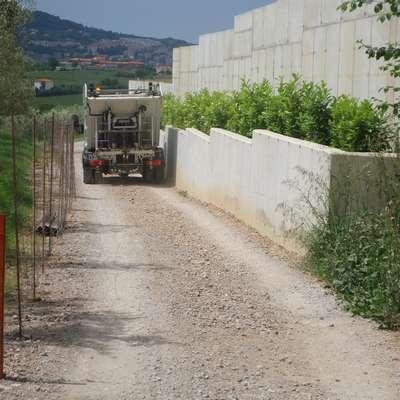 Kovinska žica je napeta na stebričkih na eni strani, betonski zid je  na drugi strani, vmes pa povsem zožena pot. Foto: Nataša Hlaj