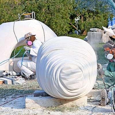 Makedonski kipar Sašo Sazdovski (v ozadju) in njegov turški  kolega Cagdas Sari na delovišču Forma vive na Seči.  Foto: Tomaž Primožič/Fpa