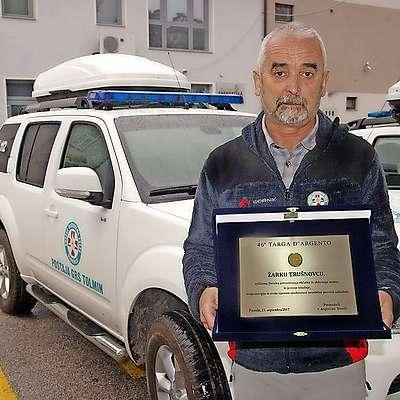 Žarko Trušnovec  z nagrado za solidarnost pred svojim  drugim domom, postajo GRS Tolmin.  Foto: Miljko Lesjak