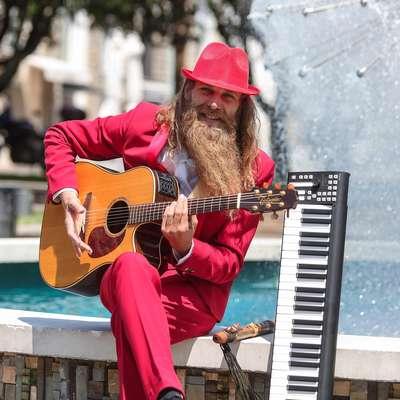S svojim novim videzom bradatega dolgolasca v rdeči obleki s klobukom je Matija Jahn pravi magnet za poglede.