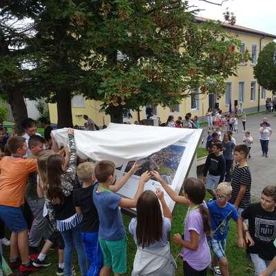 Šolarji so skupaj z županjo  pred šolo odkrili tablo z načrti za novo  večnamensko in balinarsko dvorano ter nogometno igrišče.  Foto: Helena Race